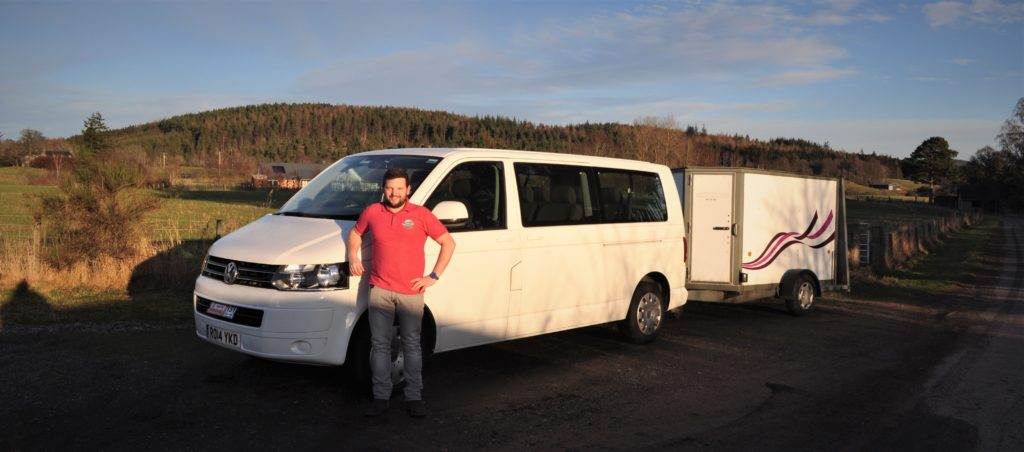 Driver guide standing in front of white vw mini bus and trailer